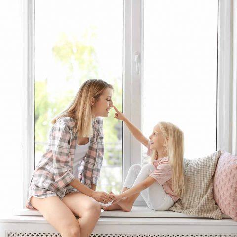 mère fille devant fenêtre lumineuxe pvc double vitrage
